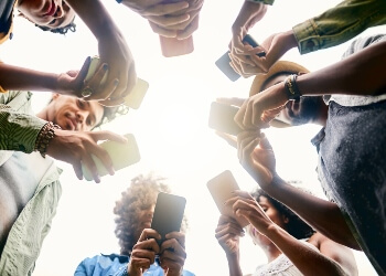 players-gather-around-in-a circle-with-cell-phones-in-their-hands